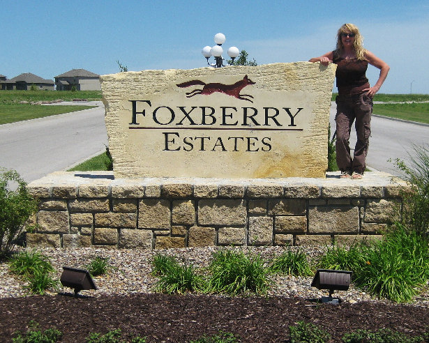 Carol, the owner in front of a sandblasted limestone entry way sign